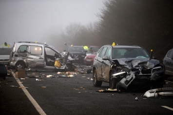 Members of the emergency services work at the scene of a multiple car collision on a main road in heavy fog near Witney, northwest of London, on December 28, 2016. At least one person died and over a dozen were injured in a pile-up involving around 20 vehicles on a major road in Southern England. / AFP PHOTO / Daniel LEAL-OLIVAS
